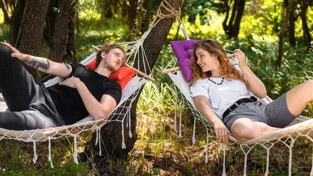 Giovane coppia sdraiata su amache, guardandosi l'un l'altro e sorridendo. verde intorno. glamping