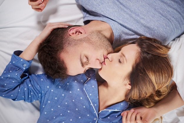 Young couple lying head to head on bed