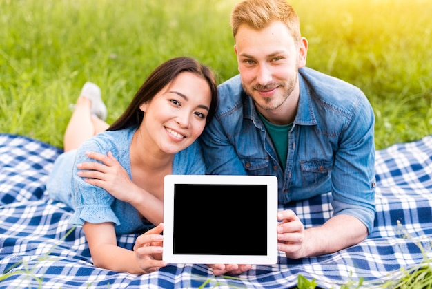 Young couple lying holding tablet