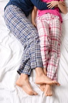 Молодая пара, лежа в постели, вид сверху