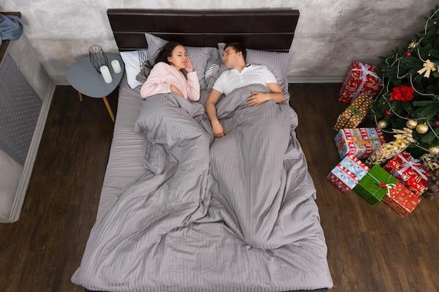 ベッドサイドテーブルの近くのベッドに横たわっている若いカップル、灰色のロフトスタイルのキャンドルとプレゼント付きのクリスマスツリー