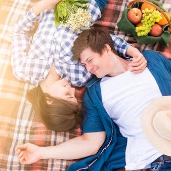 Молодая пара лежит на одеяле в лесу