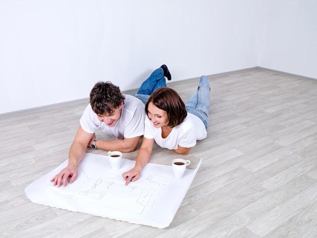 床に横になって部屋の計画を見ている若いカップル