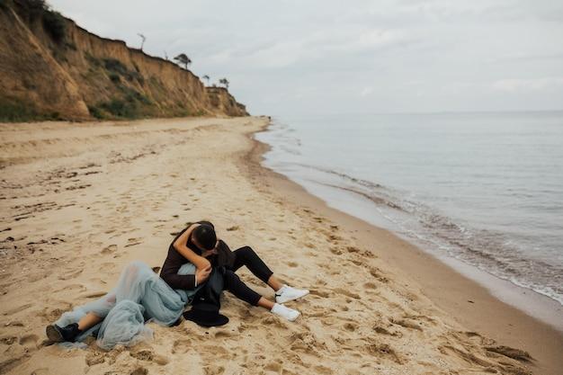 젊은 커플 해변에서 모래에 누워 키스.