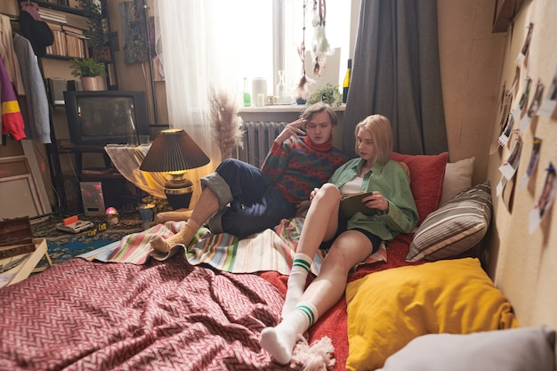 Young couple lying together on bed and reading a book together in the domestic room