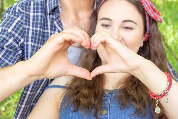手でハートを作る若いカップル。出会い愛夏ピクニック