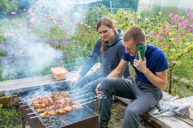 彼らの庭でバーベキューをしている若いカップル。肉を調理する男。