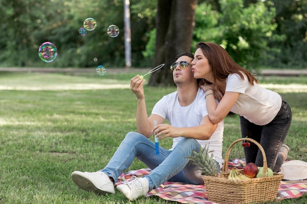 Young couple making bubbles at picnic