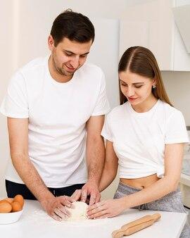 Молодая пара делает тесто