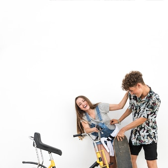 Young couple making fun with her girlfriend holding skateboard and bicycle