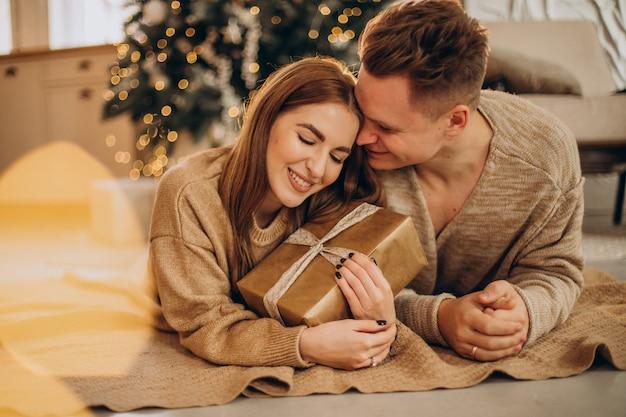 クリスマスツリーでお互いに贈り物をする若いカップル