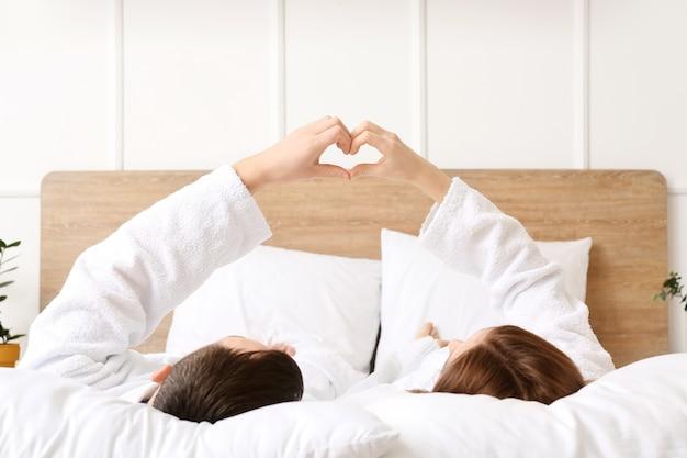Молодая пара, делая форму сердца своими руками, лежа в постели
