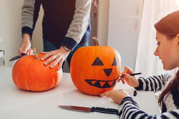 Young couple making jack-o-lantern for halloween on kitchen. drawing and cutting pumpkin