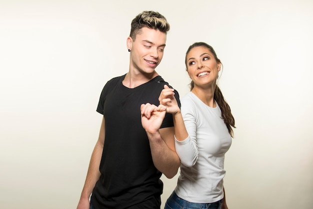 Young couple making pinkie promise on white background