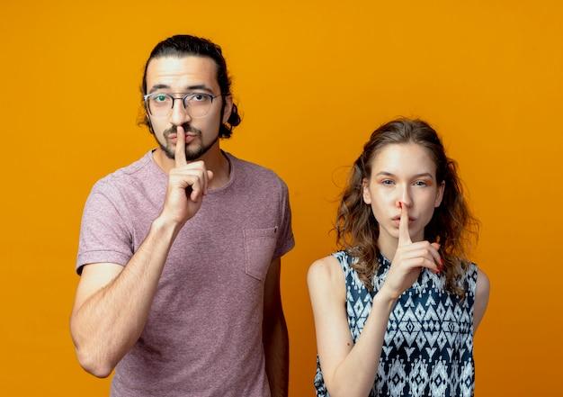 Giovani coppie che fanno gesto di silenzio con le dita sulle labbra in piedi sopra la parete arancione