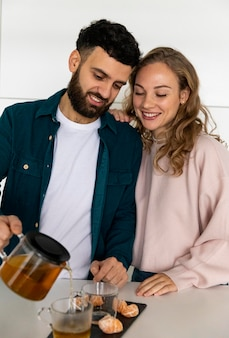 Молодая пара вместе заваривает чай дома