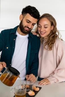 Giovani coppie che preparano il tè a casa insieme