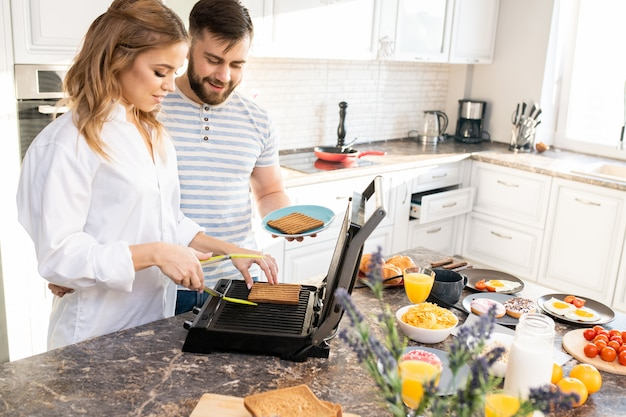 Young couple making toasts in kitchen