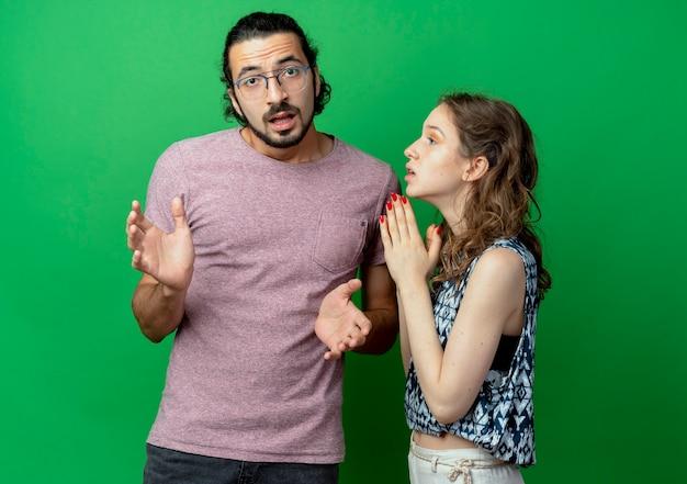 若いカップルの男性と女性、彼のガールフレンドが緑の背景の上に一緒に立っている手で希望の表現で彼に尋ねている間、カメラを見て混乱した男
