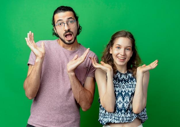 젊은 부부 남자와 여자, 녹색 벽 위에 서있는 측면에 팔을 확산 혼란