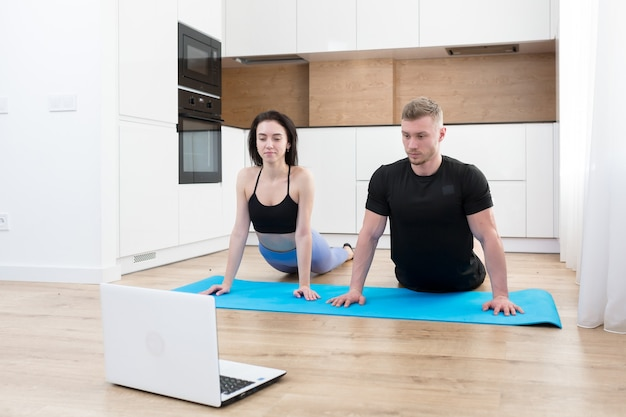 젊은 부부 남자와 여자 집에서 피트니스를 하 고 집에서 온라인으로 노트북을 사용 하여, 집에서 바닥에 트레이너와 함께 온라인 스포츠