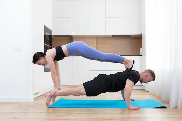 젊은 부부 남자와 여자는 바닥에 집에서 함께 피트니스를하고, 두 사람은 스포츠 매트에 부엌에서 스포츠 운동을 하