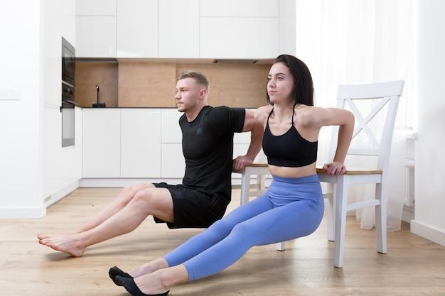 若いカップルの男性と女性が床で自宅で一緒にフィットネスをしている、2人がスポーツマットのキッチンでスポーツ運動をしている