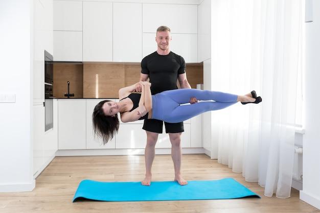 바닥에 집에서 함께 피트니스를 하 고 젊은 부부 남자와 여자, 스포츠 매트에 부엌에서 스포츠 운동을하는 두 사람