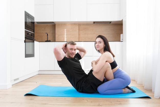 Молодая пара мужчина и женщина вместе занимаются фитнесом дома на полу, два человека делают спортивные упражнения на кухне на спортивном коврике