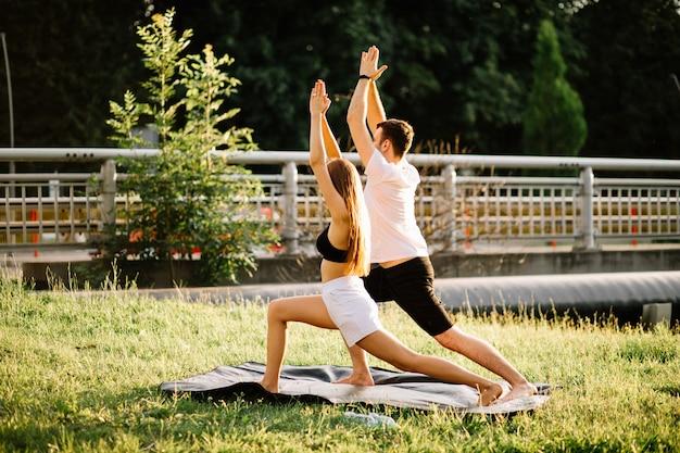 스포츠를 하는 젊은 남녀, 도시 잔디밭에서 요가, 여름 저녁, 일몰에 함께 스트레칭, 도시 생활 방식