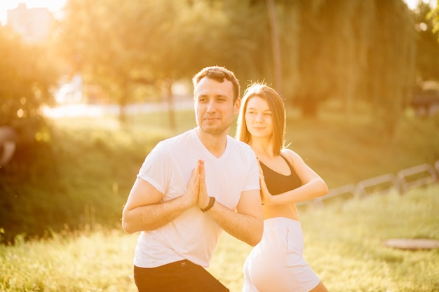 스포츠를 하는 젊은 남녀, 도시 잔디밭에서 요가, 여름 저녁, 일몰에 함께 스트레칭, 일몰에 집중