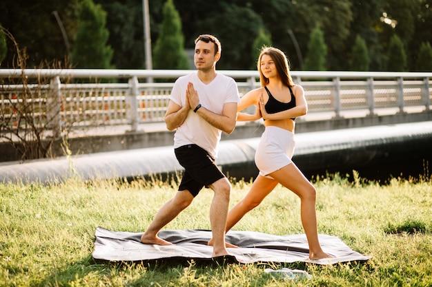 스포츠를 하는 젊은 남녀, 도시 잔디밭에서 요가, 여름 저녁, 일몰에 함께 스트레칭, 집중