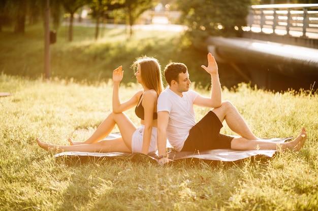 스포츠를 하는 젊은 부부 남녀, 도시 잔디밭에서 요가, 여름 저녁 함께