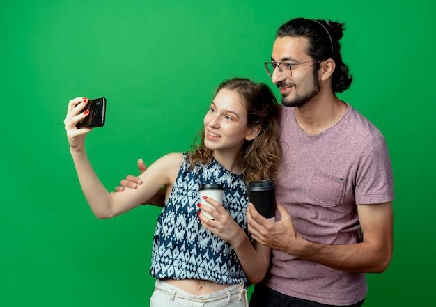 젊은 부부 남자와 사랑에 행복 한 여자, 행복한 여자가 녹색 배경 위에 서있는 스마트 폰을 사용하여 사진을 찍는