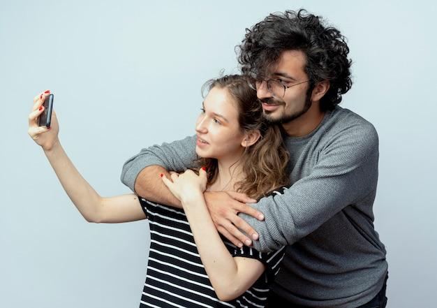 恋に幸せな若いカップルの男性と女性、白い壁の上に立っているスマートフォンを使用してそれらの写真を撮る幸せな女性