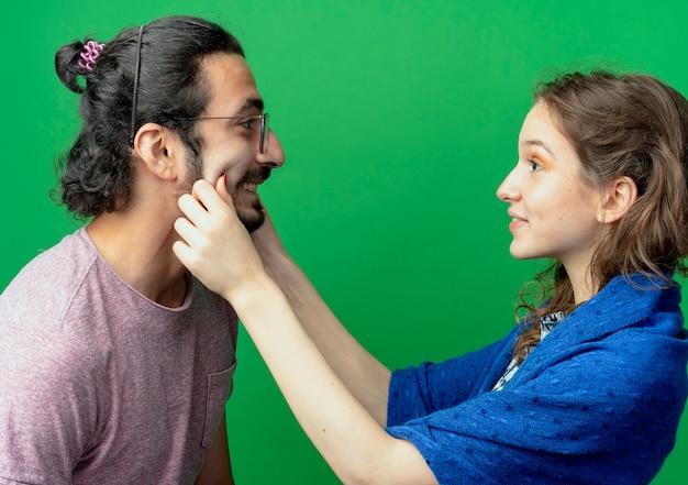恋に幸せな若いカップルの男性と女性、緑の壁の上に立っている彼女のボーイフレンドの頬を絞る女性