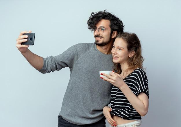 若いカップルの男性と女性、彼のガールフレンドが白い壁の上にコーヒーを飲みながら彼の隣に立っている間彼のスマートフォンを使用してそれらの写真を撮る幸せな男