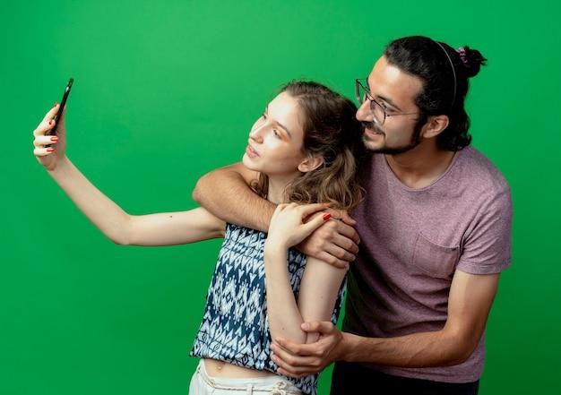 젊은 부부 남자와 여자, 녹색 배경 위에 서있는 그녀의 스마트 폰을 사용하여 사진을 찍는 행복한 여자