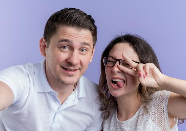 青い壁の上に立っているvサインを示して一緒に楽しんでいる若いカップルの男性と女性