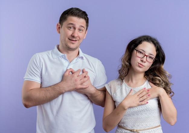 若いカップルの男性と女性が胸に手をつないで、青い壁の上に立って感謝の幸せと前向きな気持ちを感じます