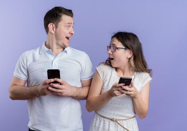 Молодая пара мужчина и женщина, держащая смартфоны, глядя друг на друга, удивлены и счастливы, стоя у синей стены