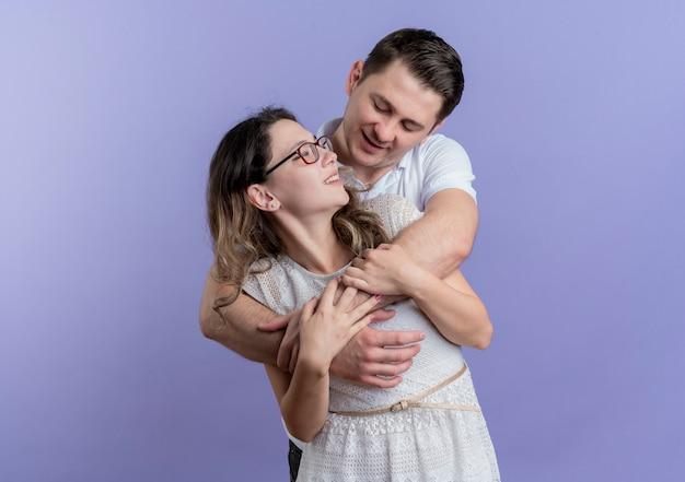 Молодая пара мужчина и женщина обнимаются счастливы в любви, весело улыбаясь над синим