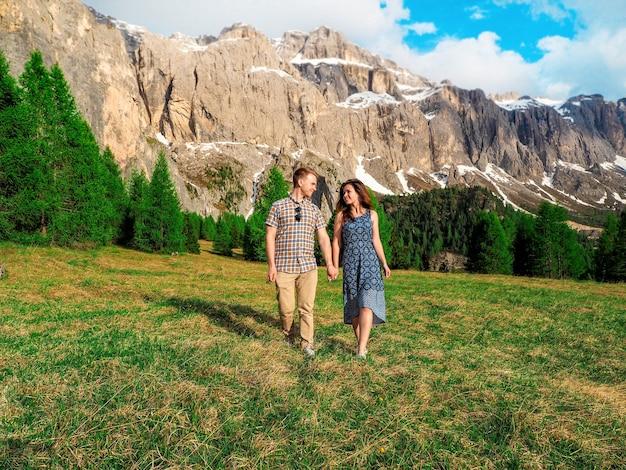 若いカップルの男性と女性が抱擁し、イタリア、ドロミテの芝生の上を歩く