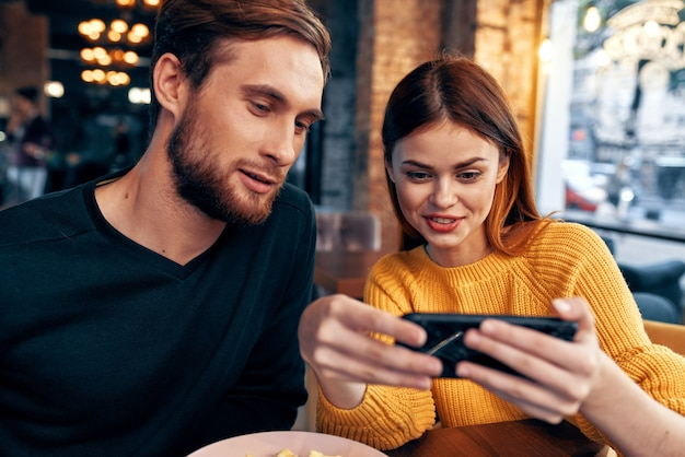 手照明で食べ物と携帯電話を注文するレストランで若いカップルの男性と女性。高品質の写真