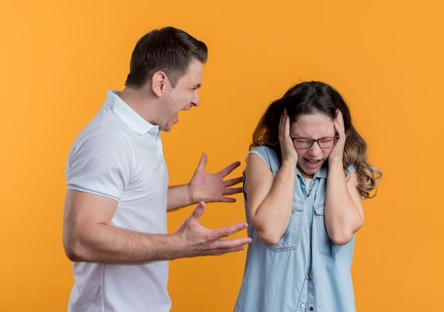 オレンジ色の彼の混乱したガールフレンドに怒って叫んでカジュアルな服を着た若いカップルの男性と女性