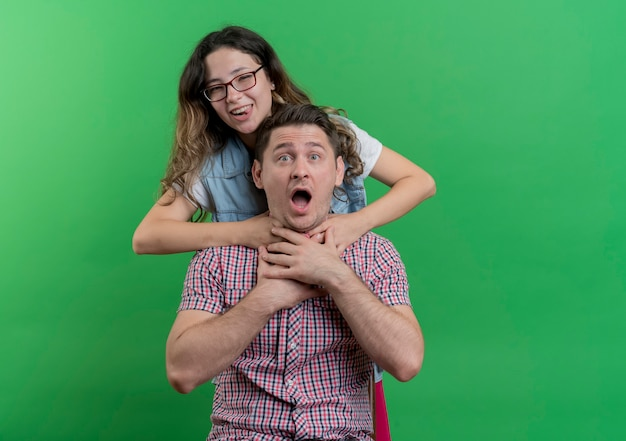 젊은 부부 남자와 여자 캐주얼 옷 쾌활한 여자 녹색 벽 위에 서 그녀의 혼란 남자 친구 목 주위에 hnads를 들고 농담
