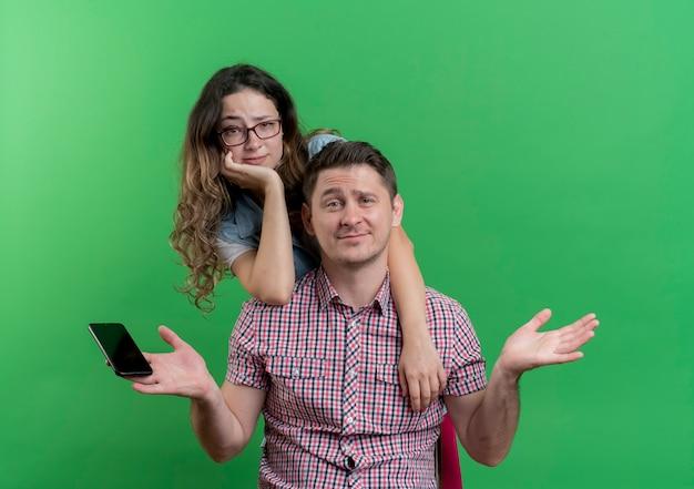 젊은 부부 남자와 캐주얼 옷에 여자는 녹색 벽에 회의적인 표정으로 엿보기 그 뒤에 서있는 스마트 폰과 그의 여자 친구를 들고 혼란 스 러 워 남자