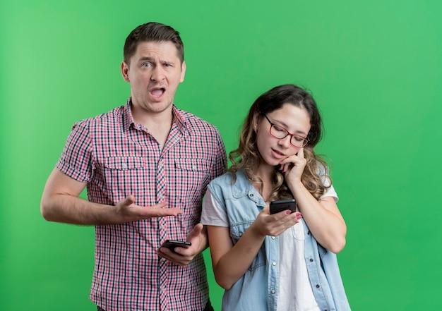 젊은 커플 남자와 캐주얼 옷에 여자는 녹색 벽 위에 서있는 휴대 전화에 말하는 그의 바쁜 girlfrined에서 팔을 가리키는 남자를 혼란
