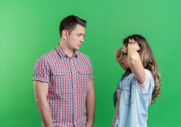 젊은 부부 남자와 캐주얼 옷에 여자 녹색 벽 위에 서있는 그녀의 혼란 여자 친구를보고 슬픈 표정으로 남자를 불쾌하게