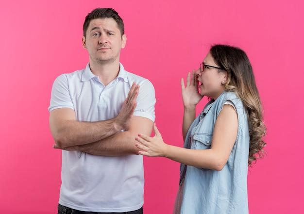 カジュアルな服装の若いカップルの男性と女性は、彼がピンクの壁の上に立って停止ジェスチャーをしている間、彼女のボーイフレンドに叫んでいる女性を不快にさせました